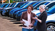 Two women discuss car loan application at auto dealership